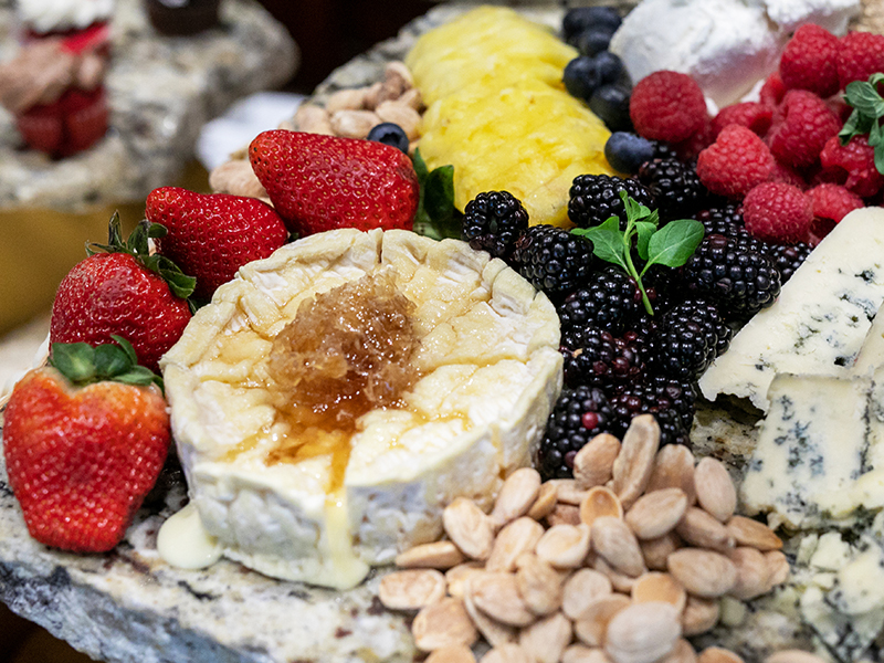 A cheese plate embelleshed with mixed berries.